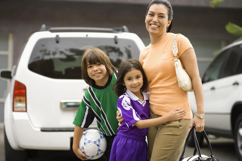 Mom with 2 children dressed for volleyball is shown standing next to a car